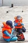 Sweden, Stockholm Archipelago, Grasko, Boys (4-5, 6-7) playing with fishing equipment on jetty