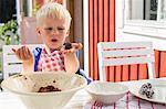 Sweden, Stockholm Archipelago, Grasko, Boy (4-5) cooking outdoors