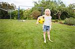 Sweden, Vastergotland, Lerum, Portrait of girl (8-9) with soccer ball standing in backyard