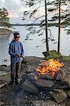 Sweden, Vastergotland, Lerum, Boy (12-13) making bonfire by lake Harsjon at sunset