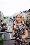 Sweden, Stockholm, Sodermalm, Hornstull, Portrait of woman standing on balcony holding digital tablet