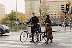 Sweden, Uppland, Stockholm, Vasastan, Vanadisplan, Two young people with bicycles walking through zebra crossing