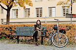 Sweden, Uppland, Stockholm, Vasastan, Rodabergsbrinken, Young woman sitting on bench using tablet