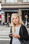 Sweden, Skane, Malmo, Teenage girl (14-15) using smart phone on street
