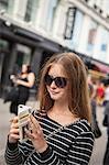 Denmark, Copenhagen, Teenage girl ( 16-17) using smart phone