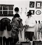Sweden, Teenage girl (14-15) and woman preparing saddle