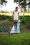 Sweden, Ostergotland, Mature woman harvesting vegetables