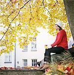 Finland, Helsinki, Kallio, Woman under maple tree, holding two fallen leaves