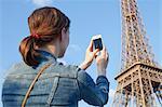 France, Ile-de-France, Paris, Rear view of woman taking picture of Eiffel Tower