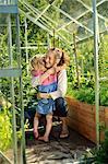Finland, Heinola, Paijat-Hame, Woman embracing girl (4-5) in glasshouse