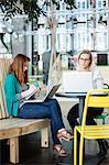 Finland, Helsinki, Women using laptops in cafe