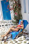 Greece, Cyclades, young woman sunbathing on a deckchair
