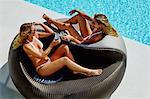Two beautiful women relaxing by the pool.