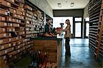 Cobbler serving female customer in traditional shoe shop