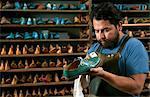Male cobbler in traditional shoe shop polishing green brogue