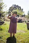 Sweden, Skane, Girl (4-5) standing in garden holding fern leaf