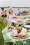 Sweden, Uppland, Roslagen, Girl (6-7) next to picnic table