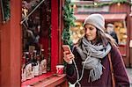 Sweden, Stockholm, Gamla Stan, Woman using phone at market