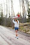 Sweden, Uppland, Lanna, Girl (12-13) carrying plane over head