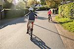 Sweden, Vastergotland, Lerum, Children (10-11, 12-13) cycling in sunny day
