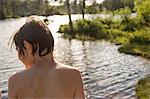 Sweden, Narke, Kilsbergen, Bjorktjarn, Rear view of shirtless boy (12-13) in front of lake