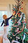 Finland, Girl (4-5) decorating christmas tree