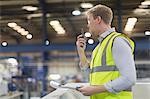 Supervisor using walkie-talkie in steel factory