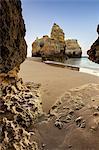 A sea cave frames the ocean and the imposing cliffs at dawn, Praia da Rocha, Portimao, Faro district, Algarve, Portugal, Europe