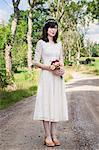 Sweden, Smaland, Vetlanda, Holsbybrunn, Portrait of bride standing on road