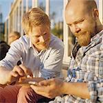 Sweden, Stockholm, Two men using mobile phone