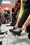 Sweden, Young woman tying shoelaces in locker room