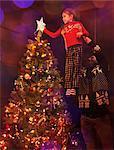 Father lifting daughter placing star on Christmas tree