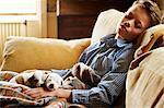 Boy and puppies sleeping on sofa