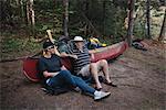 Senior couple relaxing beside canoe