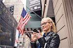 Woman on street reading texts on smartphone, New York, USA