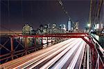 Elevated view of traffic light trails crossing Manhattan Bridge at night, New York, USA