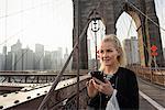 Female tourist smartphone texting on Brooklyn Bridge, New York, USA
