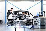 Engineers building car in racing car factory