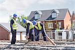 Apprentice builders digging on building site
