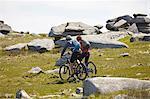 Cyclists cycling on rocky hillside