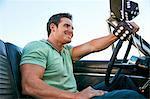 Man in convertible car looking away smiling, Los Angeles, California, USA