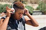 Woman wearing headphones holding smartphone looking down