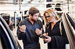 Mechanic assisting customer in using mobile app at auto repair shop