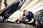 Senior mechanic holding mobile phone while repairing car at shop