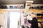 Side view of senior repairman repairing bicycle in workshop
