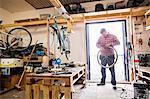 Full length of man repairing bicycle tire while standing at doorway in workshop