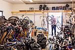 Rear view of repairman carrying bicycle at doorway of workshop