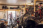 Rear view of repairman carrying bicycle at workshop