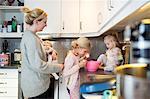 Family preparing pancake in domestic kitchen