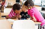Children using digital tablet in classroom